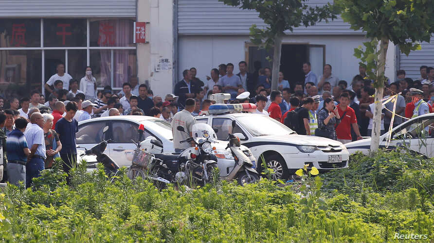 Onlookers and security personnel gather near the scene of an explosion at a kindergarten in Fengxian County in Jiangsu Province, China, June 16, 2017.