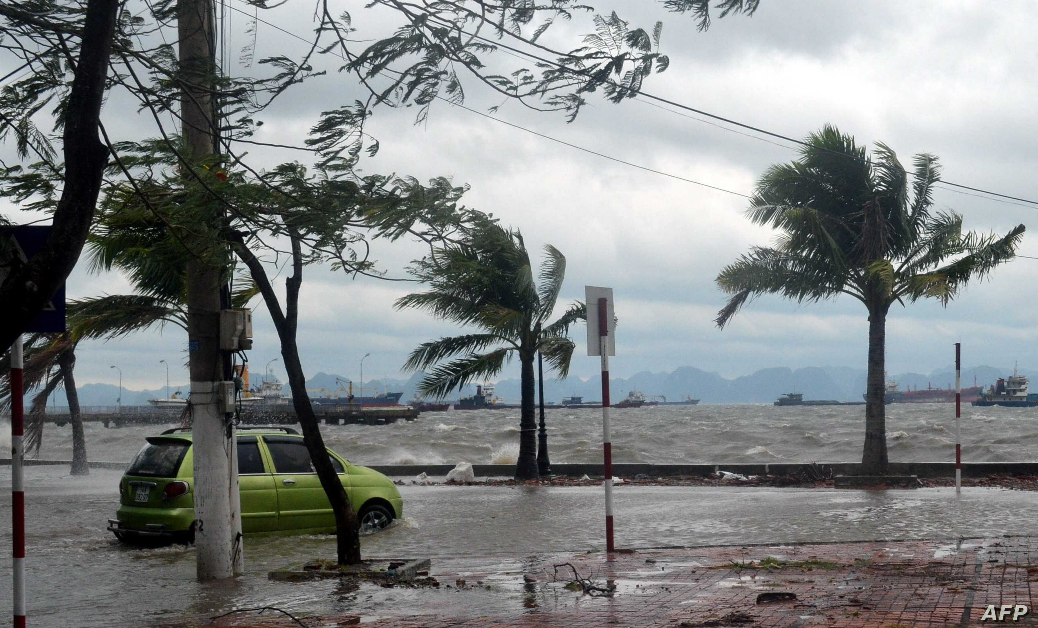 A taxi negoiates a flooded coastal road at Ha Long city, in the north-eastern coastal province of Quang Ninh, after the passage of the typhoon Haiyan, Nov. 11, 2013.