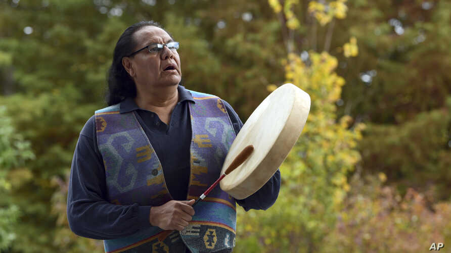 Dennis Zotigh poses outside the National Museum of the American Indian in Washington, Nov. 3, 2017. Many tribes even have their own national anthems known as flag songs that focus on veterans.