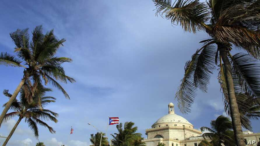 In this July 29, 2015, file photo, U.S. and Puerto Rican flags fly in front of Puerto Rico's Capitol as in San Juan, Puerto Rico.