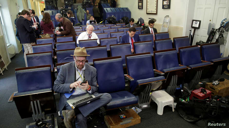 FILE - Glenn Thrush (L), chief White House political correspondent for the The New York Times, works in the briefing room after being excluded from a gaggle at the White House in Washington, February 24, 2017.