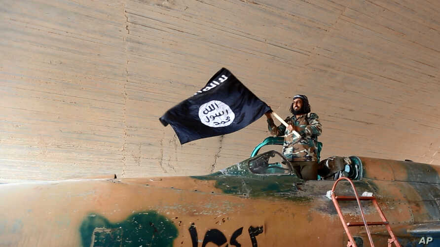 This undated image posted on Aug. 27, 2014 by the Raqqa Media Center of the Islamic State group, a Syrian opposition group, which has been verified and is consistent with other AP reporting, shows a fighter of the Islamic State group waving their fla