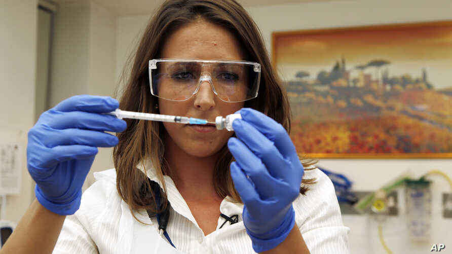Dr Felicity Hartnell, who is a clinical research fellow at Oxford University, holds a vial of an experimental vaccine against Ebola in Oxford, England, Sept. 17, 2014.