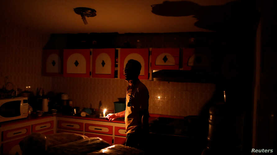 Americo Fernandez uses a candle to illuminate the kitchen at his home during a blackout in Maracaibo, Venezuela, July 25, 2018.