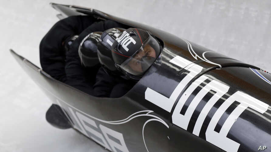 The team from the United States USA-1, piloted by Steven Holcomb, take a curve during the men's four-man bobsled training at the 2014 Winter Olympics, Feb. 21, 2014.