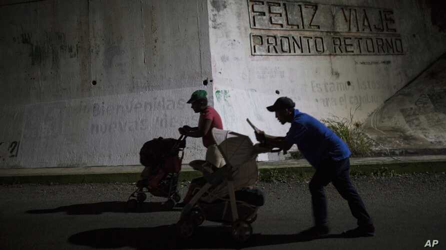 Joel Eduardo Espinar, foreground, and his wife, Yamilet Hernandez, push baby strollers as they start early in the morning toward Arriaga from Pijijiapan, Mexico, Oct. 26, 2018.
