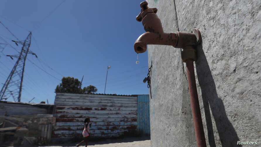 FILE - Residents walk past a leaking communal tap in Khayelitsha township, near Cape Town, South Africa, Dec. 12, 2017.