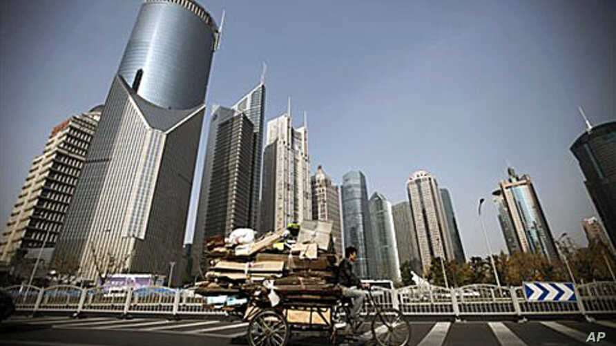 A junk collector rides his tricycle with high-rising buildings as background in Shanghai, China. The prolonged weakness in the U.S. and Europe may be the least of Asia's troubles in 2011, economists say, as the region fights potentially destabilizing