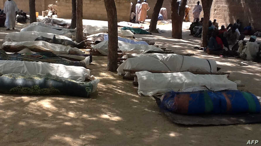 FILE - People stand next to dead bodies, laid out for burial, in the village of Konduga, in northeastern Nigeria, on Feb. 12, 2014, after an attack by Boko Haram militants killed 39 people.