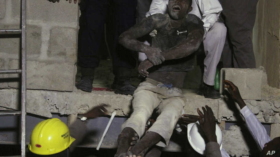 Rescue workers carry a survivor from the rubble of a building under construction which collapsed in Lagos, Nigeria, Monday, Nov, 4.  2013. Emergency officials said casualty figures from the incident were unclear as they continued their search for sur