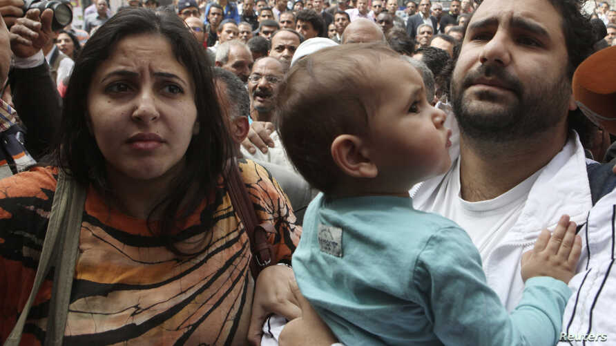 Alaa Abdel Fattah (R), one of the activists who was summoned by the public prosecutor on whether he had a role in the recent violent anti-Islamists protests, arrives with his wife and child to the public prosecutor's office in Cairo, March 26, 2013.