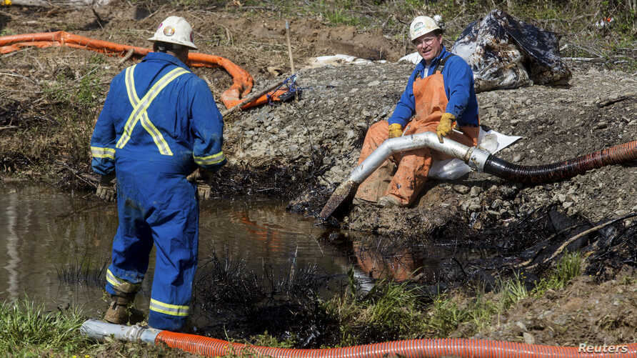Emergency crews work to clean up an oil spill near Interstate 40 in Mayflower, Arkansas. An Exxon Mobil pipeline carrying Canadian crude oil was shut off after a ruptured on Friday causing an evacuation of 22 homes, Mar. 31, 2013.