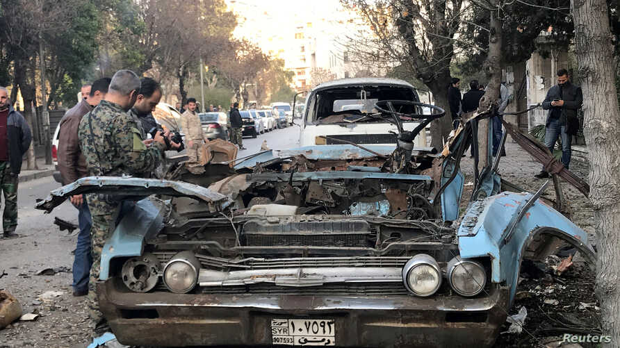 People gather at a site of a car bomb blast in Damascus, Syria, Jan. 24, 2019.