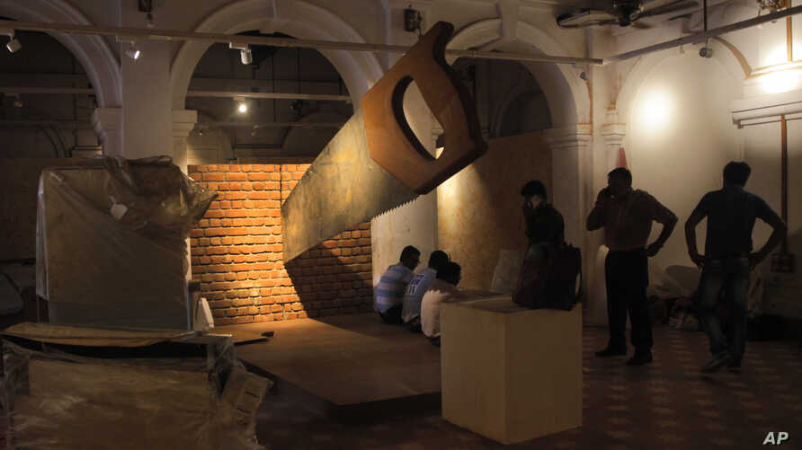 Workers stand around a giant saw installation that is cutting through a brick wall at the Partition Museum that is set to open  in Amritsar, India, 32 kilometers (20 miles) from the border with Pakistan. The artistic installation depicts the division