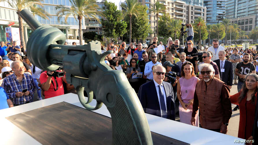 """Lebanon's Caretaker Cultural Minister Ghattas Khoury and Arun Gandhi, grandson of Mahatma Gandhi, are seen during the unveiling ceremony of a copy of Carl Fredrik Reutersward's """"Non-Violence"""" sculpture in Beirut, Lebanon, Oct. 2, 2018."""