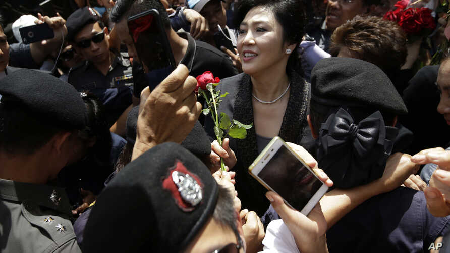 Thailand's former Prime Minister Yingluck Shinawatra, center, receives a flower from her supporter at the Supreme Court after making her final statements in a trial on a charge of criminal negligence in Bangkok, Thailand,  Aug. 1, 2017.