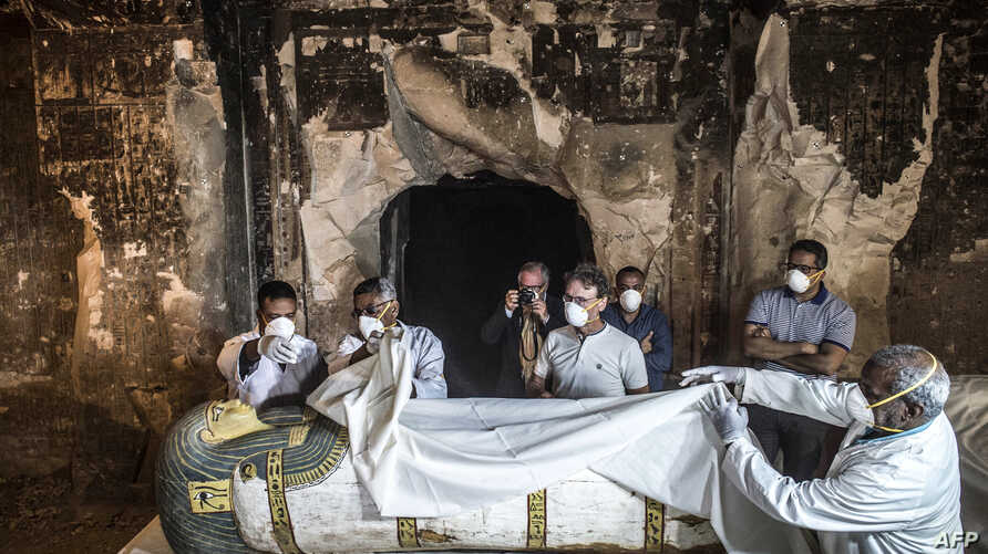 Egypt's Antiquities Minister Khaled al-Enany, right, and Mostafa Waziri, second right behind, the secretary-general of the Supreme Council of Antiquities, inspect an intact sarcophagus during its opening at the site of Tomb TT33 at Al-Assasif necropo