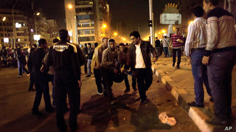 Protesters opposed to Egyptian President Mohammed Morsi evacuate and injured fellow protester during clashes between supporters of president Mohammed Morsi and their rivals in front of the president palace, in Cairo, Egypt, Wednesday, Dec. 5, 2012.