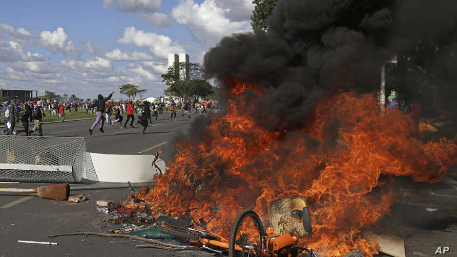 Demonstrators create a flaming barricade with chairs taken from the Ministry of Agriculture during an anti-government protest in Brasilia, Brazil, May 24, 2017. Brazil's president ordered federal troops to restore order in the country's capital ...