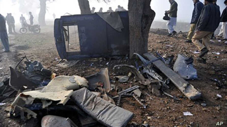 Pakistani officials examine a remains of the police vehicle damaged by a roadside bomb on the outskirts of Peshawar, Pakistan, February 8, 2011