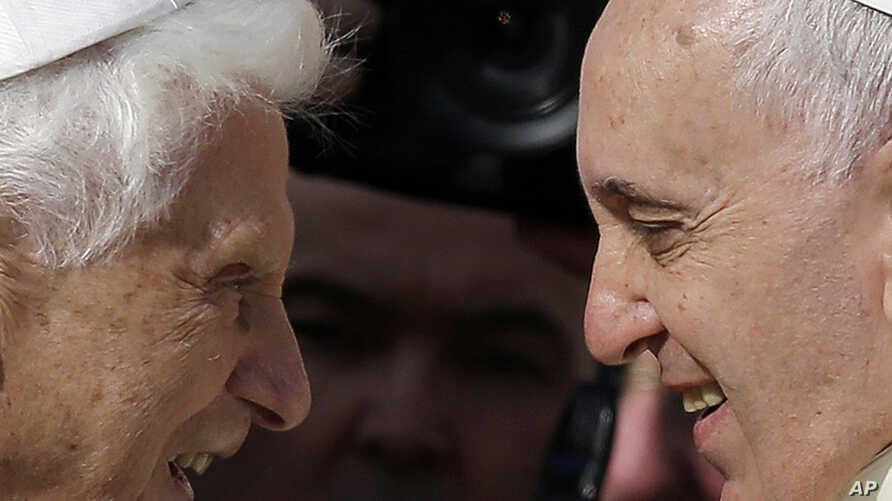 FILE - Pope Emeritus Benedict XVI, left, and Pope Francis exchange greetings at a 2014 meeting. Benedict offers views on the papacy and the Roman Catholic Church in a new book, 'The Last Conversations.'