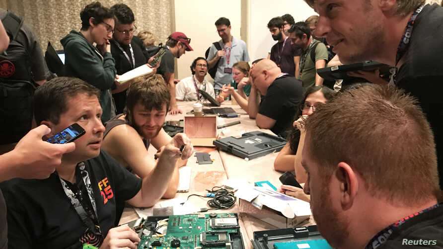 "People pull apart computers used in voting machines in a bid to uncover security bugs during a ""hacker voting village"" exercise at the Def Con conference in Las Vegas, Nevada, July 28, 2017."