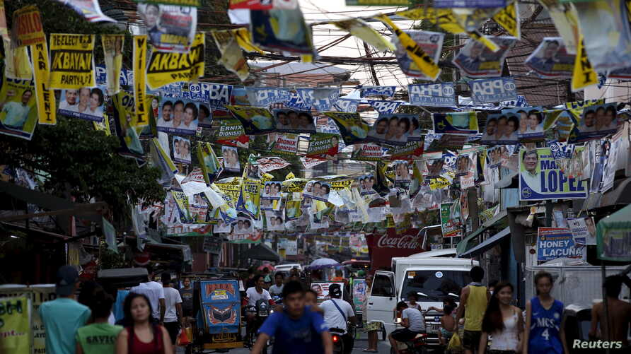 Election posters for the 2016 national elections hang above a busy road in Tondo, Manila, April 26, 2016.