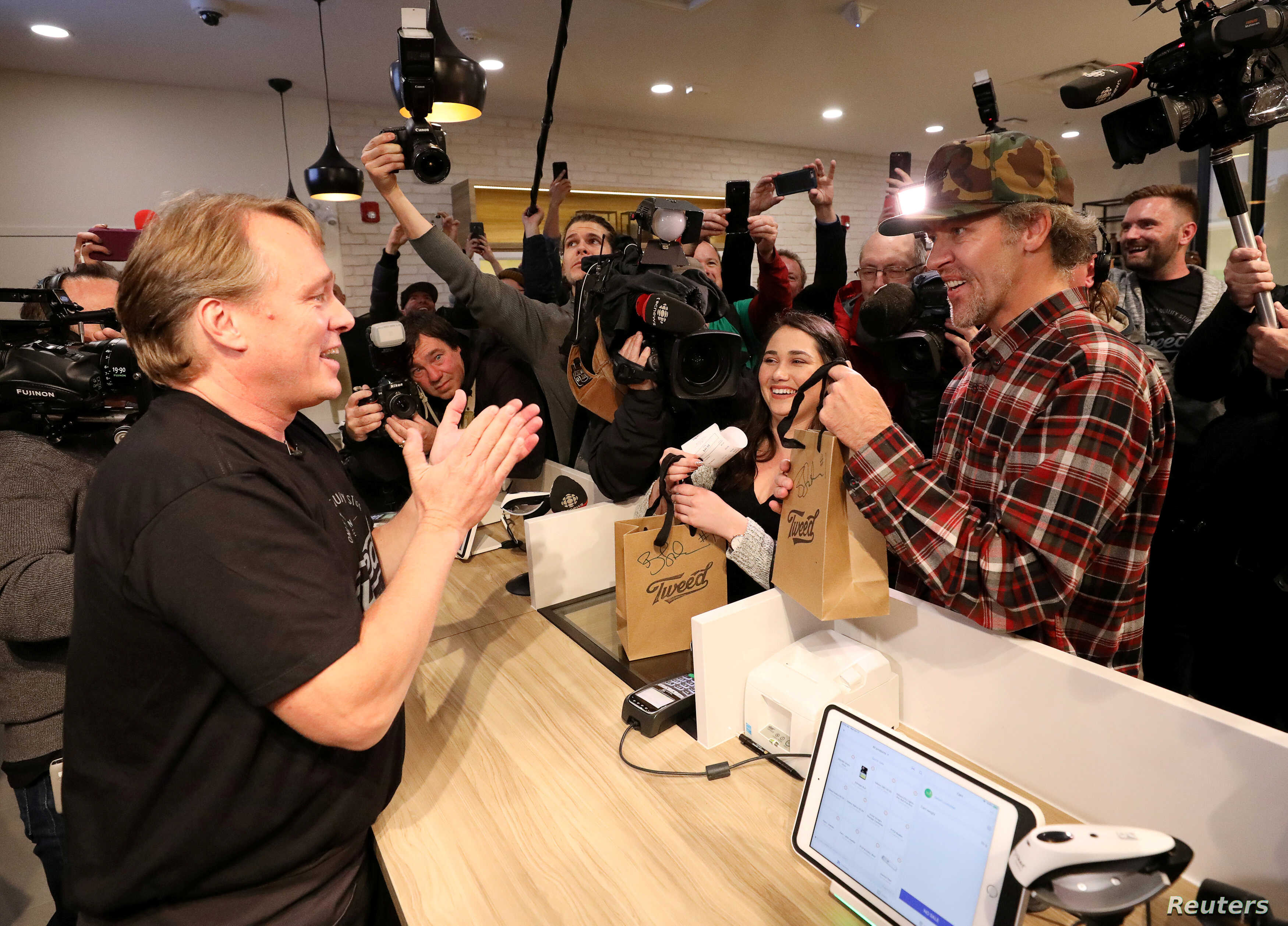 Canopy Growth CEO Bruce Linton applauds after handing Ian Power and Nikki Rose, who were first in line to purchase the first legal recreational marijuana after midnight, their purchases at a Tweed retail store in St John's, Newfoundland and Labrador,
