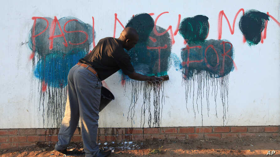 FILE - A caretaker of a building attempts to rub off anti-government graffiti in Harare, Zimbabwe, Sept. 6, 2016. Protests have rocked Zimbabwe since July, calling on President Robert Mugabe to fix the economy and respect human rights.