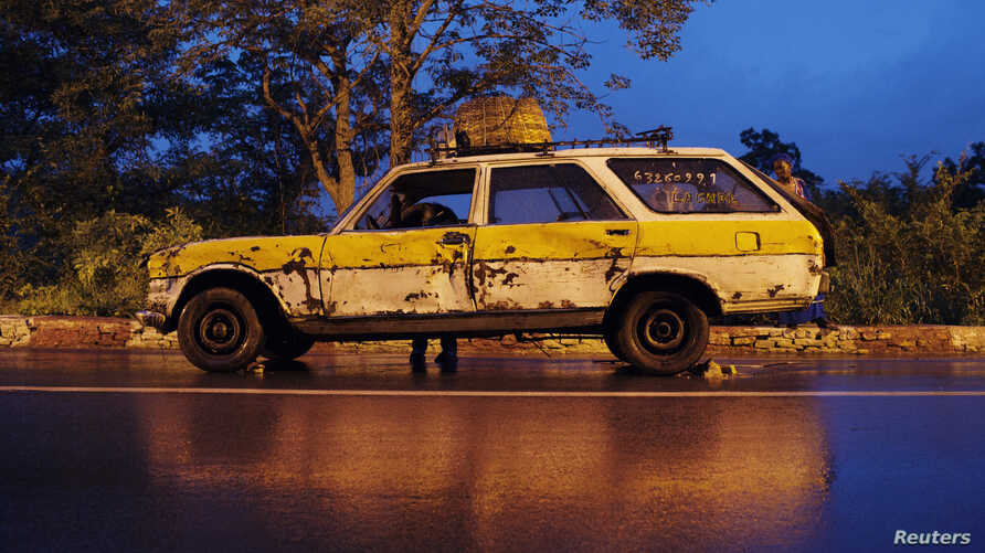 FILE - A driver looks for tools to replace a flat tire on a public transport car in Bamako, Mali.
