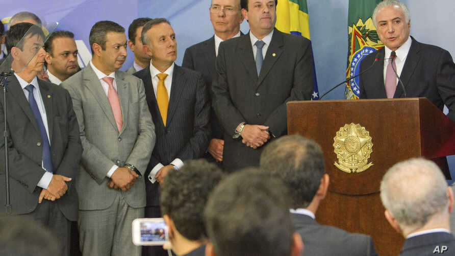 Brazil's President Michel Temer, right, reads a statement accompanied by supporters and ministers of his government, at the Planalto Presidential Palace, in Brasilia, June 27, 2017.