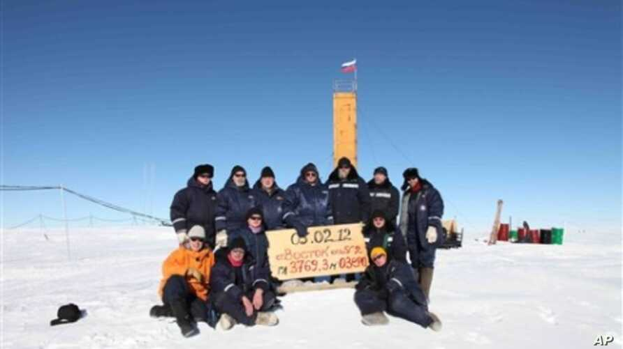 "Russian researchers at the Vostok station in Antarctica after reaching subglacial Lake Vostok. Scientists hold a sign reading ""05.02.12, Vostok station, boreshaft 5gr, lake at depth 3769.3 metres."""