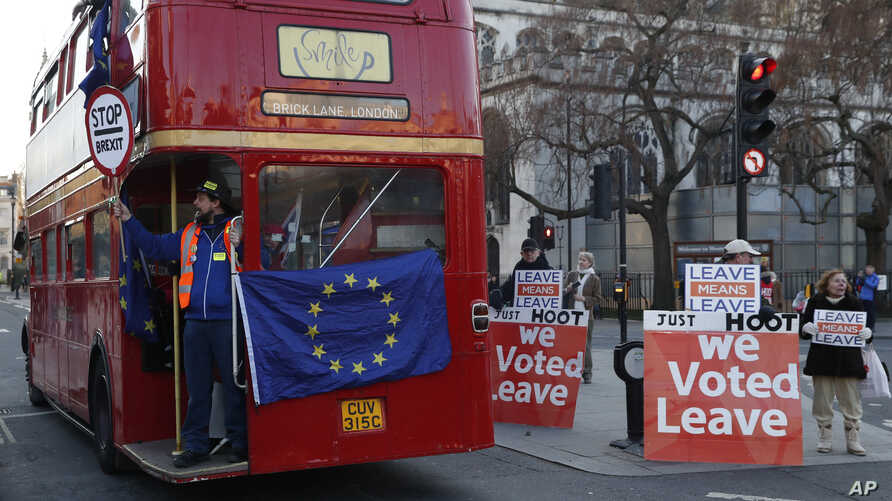 Anti-Brexit protesters on board a hired red London bus demonstrate as they drive past the Houses of Parliament in London, Jan. 28, 2019.