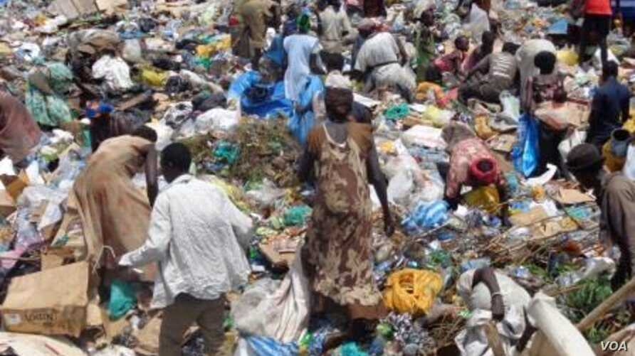 Women pick through a sea of trash outside Juba, looking for plastic bottles that they can exchange for money at a local NGO.