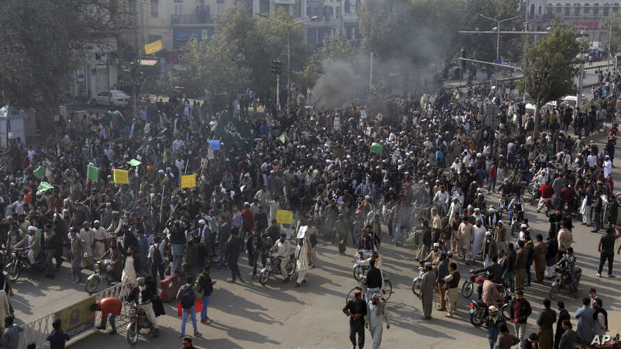 Supporters of religious groups burn tires at a rally to express solidarity with protesters block main highway in capital, Saturday, Nov. 25, 2017 in Peshawar, Pakistan.