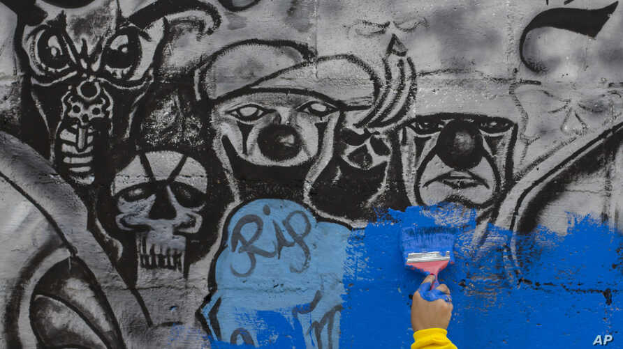 FILE - An inmate paints over gang graffiti in Soyapango, El Salvador, June 21, 2016. El Salvador saw its murder rate drop for the third year in a row. The government attributes the drop to a crackdown on crime, prevention programs in high-risk commun