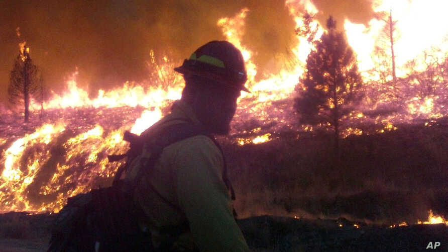 In this photo released by the U.S. Forest Service Wednesday, Aug. 14, 2013, firefighters stand watch near the perimeter of the Elk Complex fire near the small mountain community of Pine, Idaho.