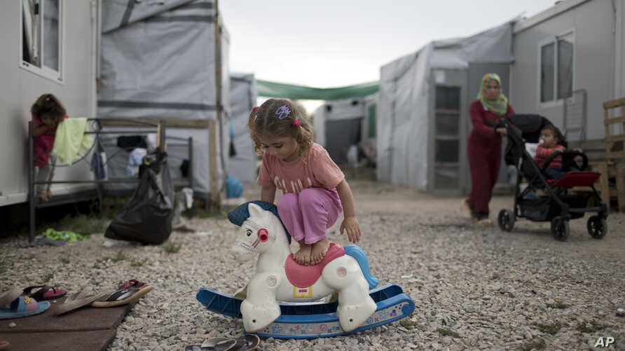 A Syrian child plays with a plastic toy horse at the refugee camp of Ritsona about 86 kilometers (53 miles) north of Athens.