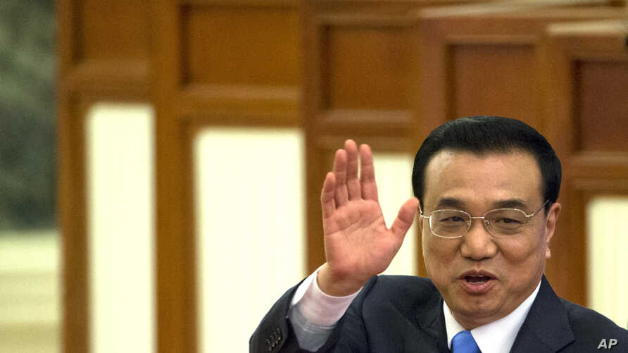 Chinese Premier Li Keqiang waves as he leaves after a press conference at the end of the National People's Congress in Beijing's Great Hall of the People, March 15, 2015.