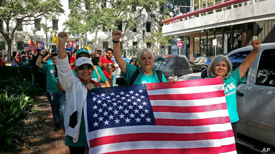 FILE - Demonstrators march outside federal court in New Orleans, Sept. 22, 2017, with immigrants and their advocates chanting and beating drums outside to protest immigration laws.