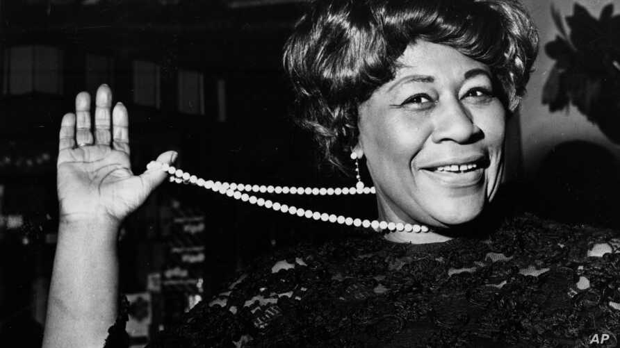 FILE - In this Feb. 22, 1968 file photo, American jazz singer Ella Fitzgerald swings her necklace as she arrives at the Carlton Theatre in London, England. The National Portrait Gallery is putting up a photograph of Fitzgerald, often referred to as ""