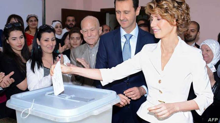 A handout picture released by the official Facebook page of Syria's First Lady Asma al-Assad shows Syrian President Bashar al-Assad (C) watching on as his wife Asma casts her vote at a polling station in Maliki.