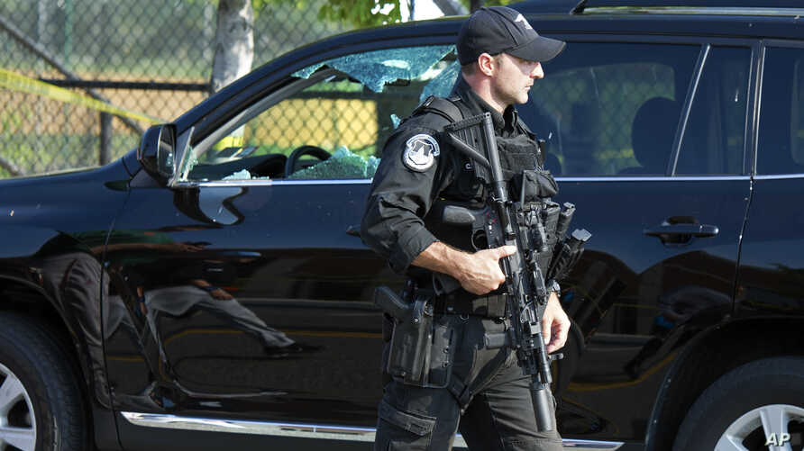 A Capitol Hill Police officer walks past an automobile with the driver's window damaged at the scene of a shooting in Alexandria, Virginia, June 14, 2017.