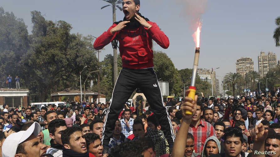 Students who are supporters of the Muslim Brotherhood and ousted President Mohamed Morsi shout slogans in front of Cairo University, March 26, 2014.