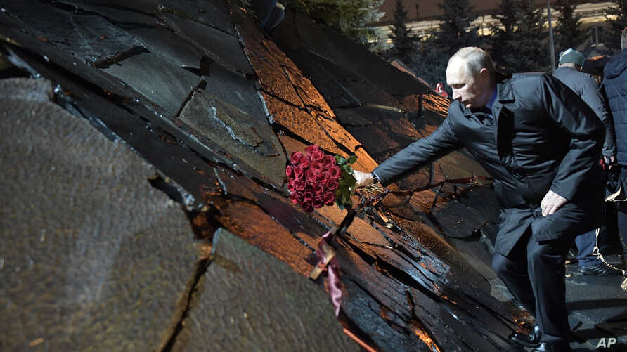 """Russian President Vladimir Putin, lays a bunch of flowers as he he attends a ceremony unveiling the country's first national memorial to victims of Soviet-era political repressions called """"The Wall of Grief"""" in Moscow, Russia, Oct. 30, 2017."""