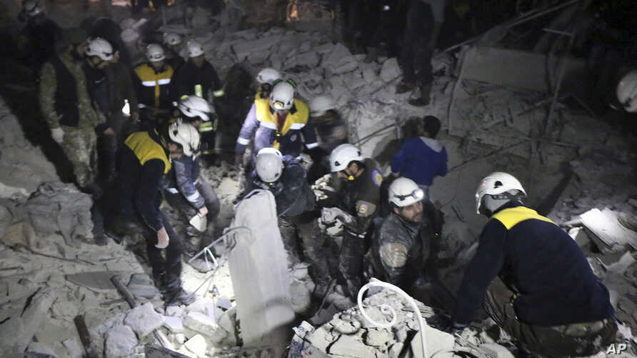 This photo provided on Jan. 7, 2018, by the Syrian Civil Defense White Helmets, which has been authenticated based on its contents and other AP reporting, shows Civil Defense workers inspecting a damaged building after a bombing in Idlib, Syria.