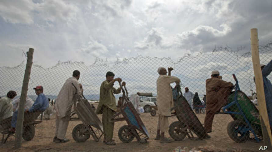 Men line up with their wheelbarrows to transport supplies for families displaced by military operations last year against militants in Bara, at the United Nations High Commission for Refugees-supported Jalozai camp in Pakistan's northwest, April 11,