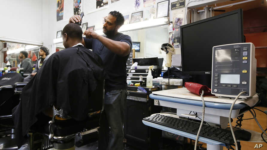FILE - Barber Eric Muhammad, owner of A New You Barbershop cuts the hair of customer Marc M. Sims before measuring his blood pressure in Inglewood, California, March 11, 2018.