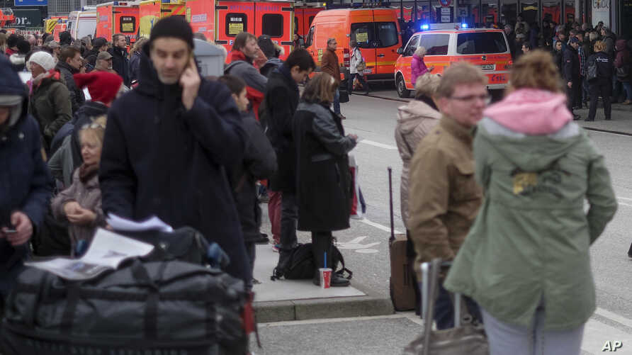 Travelers wait outside the Hamburg airport, Feb. 12, 2017 after after several people were injured by an unknown toxic that likely spread through the airports' air conditioning system.