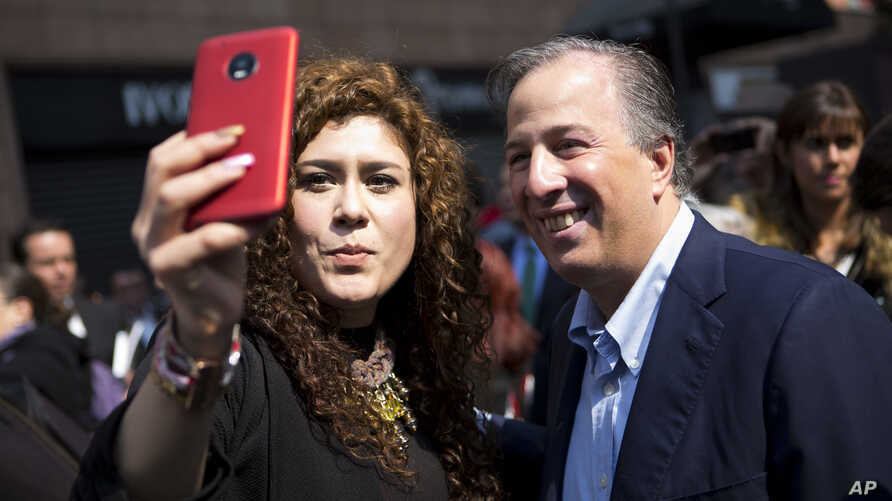 Jose Antonio Meade, right, expected presidential candidate for the ruling Institutional Revolutionary Party poses for a selfie with a supporter in Mexico City, Jan. 18, 2018. Mexico will hold general elections on on July 1, 2018.
